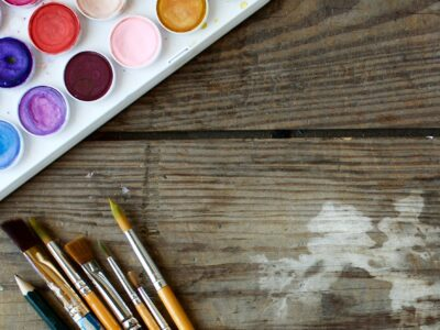 Blog featured image includes a water color palette and brushes laid on a wooden table.